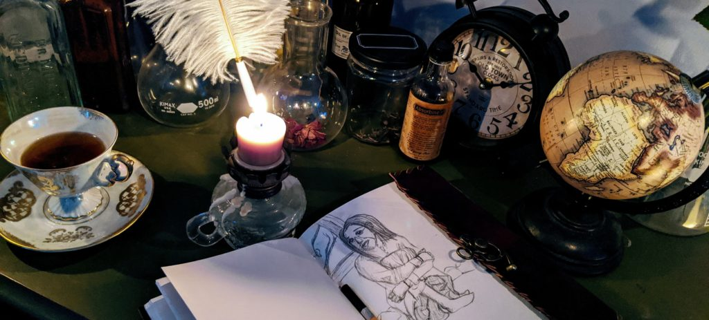 antique image of tea, candles, and a sketchbook